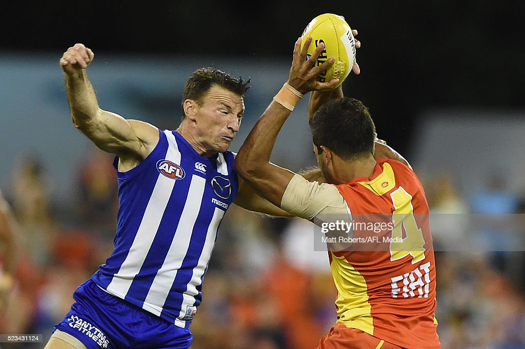 Jack Martin of the Suns is tackled by Brent Harvey of the Kangaroos during the round five AFL match between the Gold Coast Suns and the North Melbourne Kangaroos at Metricon Stadium on April 23, 2016 in Gold Coast, Australia.