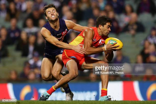 Jack Martin of the Suns is tackled by Lachie Weller of the Dockers during the round 20 AFL match between the Fremantle Dockers and the Gold Coast...