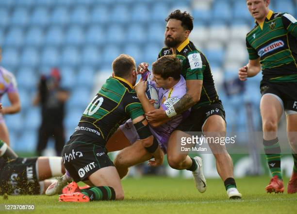 Jack Maunder of Exeter Chiefs is tackled by Dan Biggar and Matt Proctor of Northampton Saints on his way to scoring his side's first try during the...