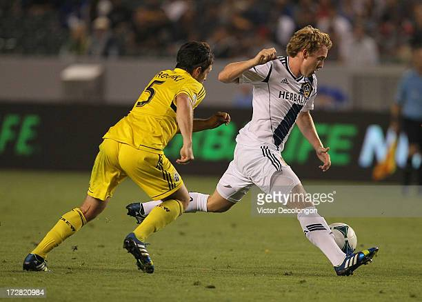 Jack McBean of the Los Angeles Galaxy paces the ball on the attack against Danny O'Rourke of the Columbus Crew in the second half of their MLS match...