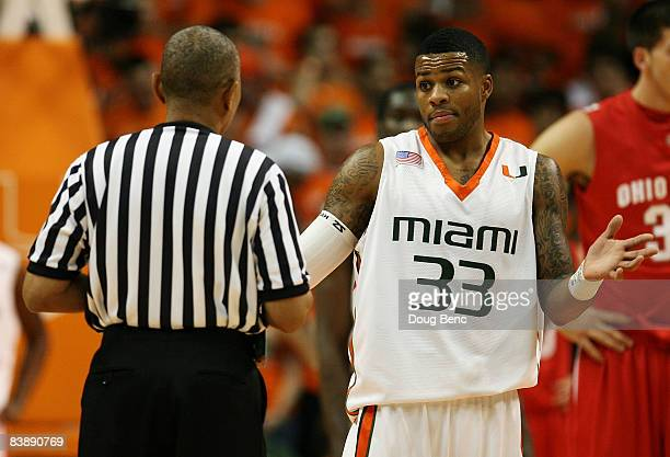 Jack McClinton of the Miami Hurricanes talks with referee Tony Greene as the other officials watch a replay while taking on the Ohio State Buckeyes...