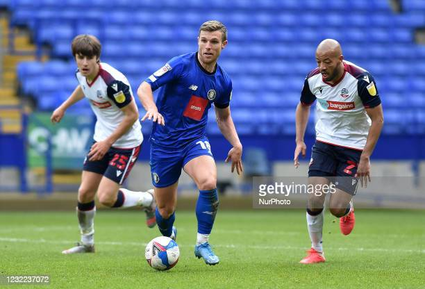 Jack Muldoon of Harrogate Town tussles with Alex John-Baptiste of Bolton Wanderers during the Sky Bet League 2 match between Bolton Wanderers and...