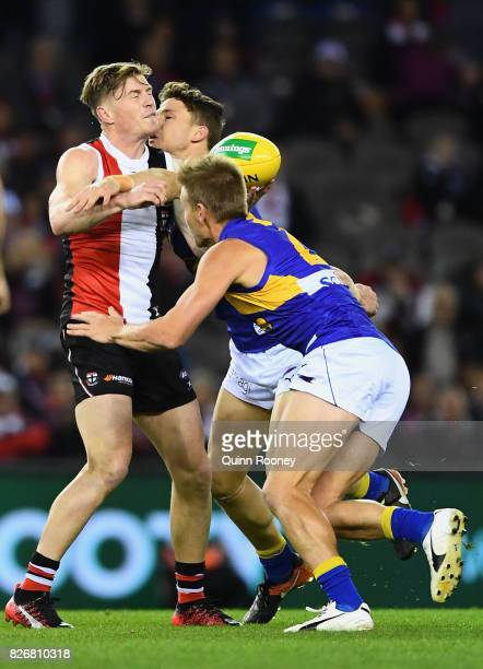 Jack Newnes of the Saints handballs whilst being tackled by Jack Redden and Mark LeCras of the Eagles during the round 20 AFL match between the St...