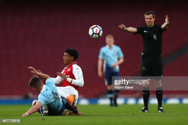 Jack Newton of Blackpool battles for possesion with Xavier Amaechi of Arsenal as match referee Craig Hicks looks on during the FA Youth Cup Semi...