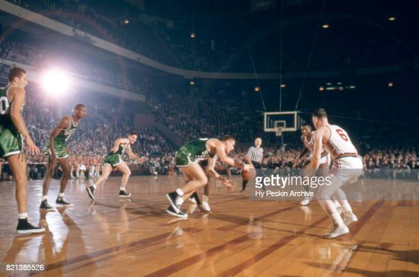 Jack Nichols of the Boston Celtics dribbles up the court as he is defended by Lou Costello and Earl Lloyd of the Syracuse Nationals during an NBA...