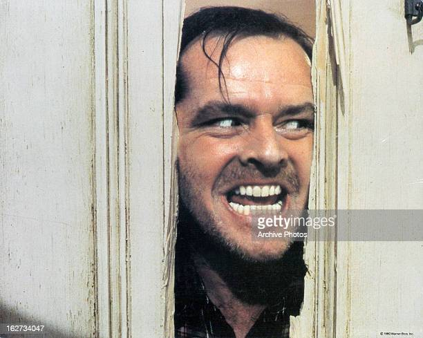 Jack Nicholson peering through axed in door in lobby card for the film 'The Shining' 1980