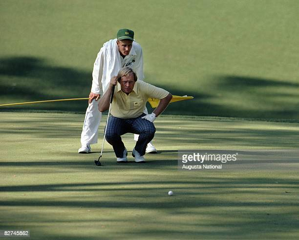 Jack NIcklaus and caddy son Jackie Nicklaus line up a putt during the 1986 Masters Tournament at Augusta National Golf Club on April 1013 1986 in...