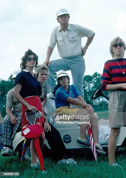 Jack Nicklaus nonplaying captain of the American team standing on top of a golf buggy surrounded by the wives of the United States team during the...