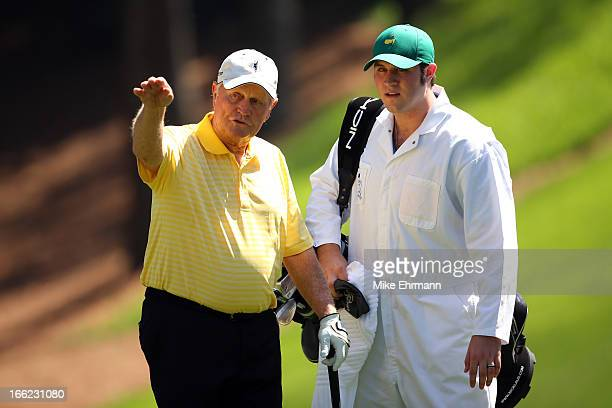 Jack Nicklaus of the United States and his caddie look at a shot during the Par 3 Contest prior to the start of the 2013 Masters Tournament at...