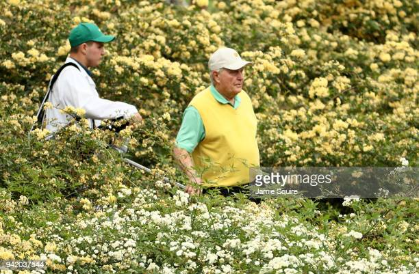 Jack Nicklaus of the United States walks with caddie and grandson Gary Nicklaus Jr among the flowers during the Par 3 Contest prior to the start of...