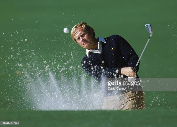 Jack Nicklaus of the USA keeps his eye on the ball as he hits out of the bunker with the sand creating a crown effect during the US Masters Golf...