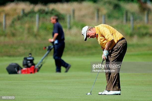 Jack Nicklaus of the USA putts on the 3rd as a greenkeeper cuts the green during practice for the 134th Open Championship, at Old Course, St Andrews...