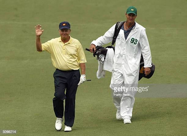 Jack Nicklaus of the USA waves as he walks to the second green with his caddie during the first round of the Masters at the Augusta National Golf...