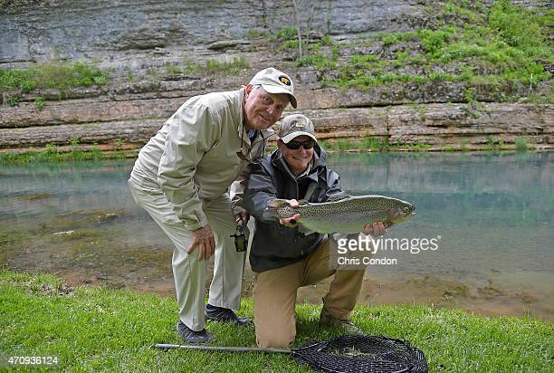 Jack Nicklaus poses with a large rainbow trout and his fishing guide during a fly fishing excursion at Dogwood Canyon after his ProAm round during...