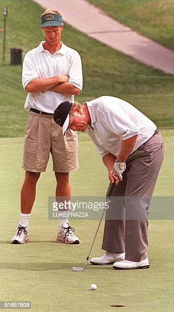 Jack Nicklaus putts as his son and caddie Jack Nicklaus II watches during the last day of practice for the 1997 US Open Golf tournament 11 June at...