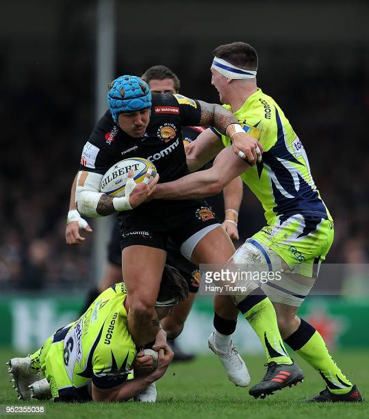 Jack Nowell of Exeter Chiefs looks to break past Ben Curry and Tom Curry of Sale Sharks during the Aviva Premiership match between Exeter Chiefs and...