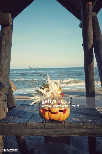 jack o lantern on table at beach - halloween beach stock photos and pictures