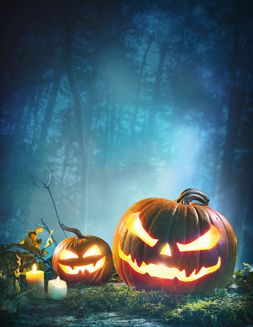 Jack o' lanterns glowing at moonlight in front of spooky forest 1049803322