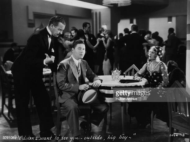 Jack Oakie is ordered to leave a nightclub by the Maitre D' in front of a bemused Jean Arthur in a scene from the ParamountPublix comedy 'Gang...