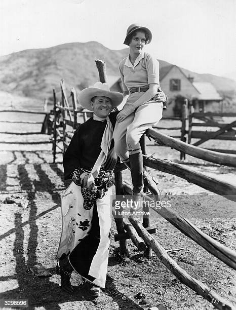Jack Oakie standing beside the ranch fence where June Collyer is sitting in a scene from 'Dude Ranch' directed by Frank Tuttle for Paramount