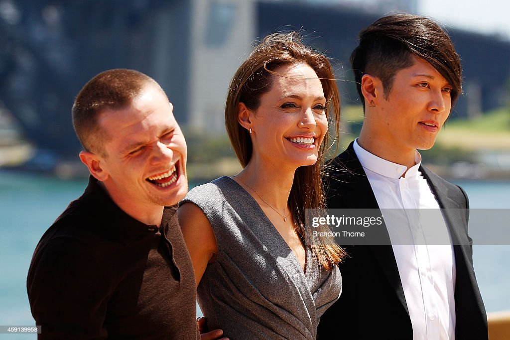 Jack O'Connell, Angelina Jolie and Miyavi Ishihara share a joke at the photo call of Unbroken at Sydney Opera House on November 18, 2014 in Sydney, Australia.