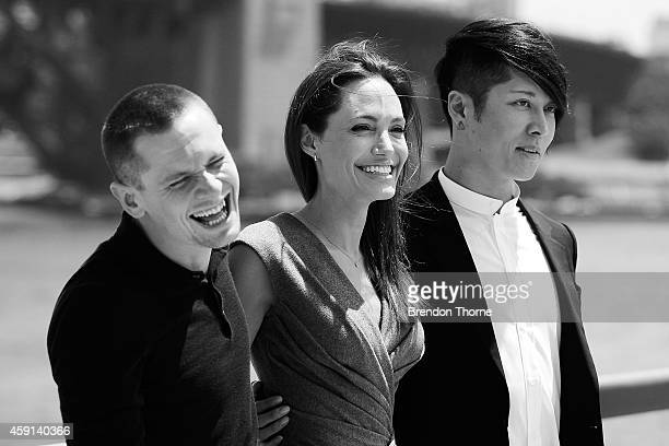 Jack O'Connell Angelina Jolie and Miyavi Ishihara share a joke at the photo call of Unbroken at Sydney Opera House on November 18 2014 in Sydney...