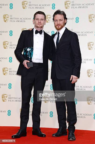 Jack O'Connell winner of the EE Rising Star award and presenter James McAvoy pose in the winners room at the EE British Academy Film Awards at The...