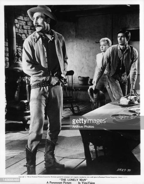 Jack Palance putting on his belt as Elaine Aiken and Anthony Perkins move towards sound they hear in a scene from the film 'The Lonely Man' 1957