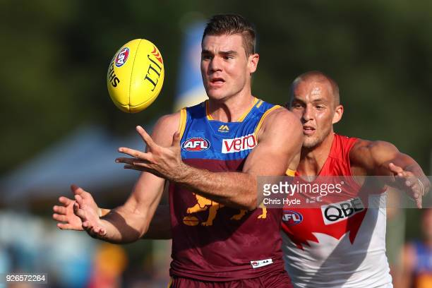 Jack Payne of the Lions is tackled by Sam Reid of the Swans during the AFL JLT Community Series match between the Brisbane Lions and the Sydney Swans...