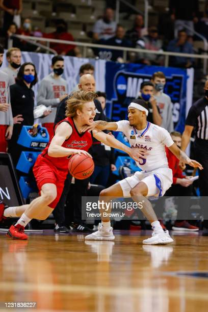 Jack Perry of the Eastern Washington Eagles drives past Dajuan Harris of the Kansas Jayhawks in the first round of the 2021 NCAA Division I Mens...