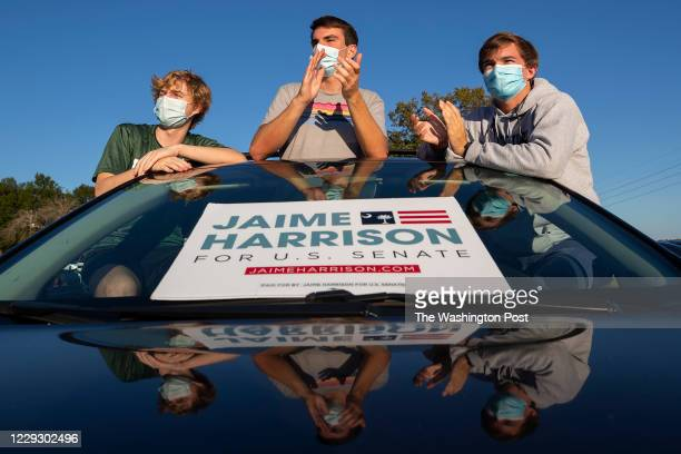 Jack Poss, Miles Brown, and Will Johnson watch from their car as Democratic candidate for U.S. Senate Jaime Harrison holds a drive-in campaign rally...