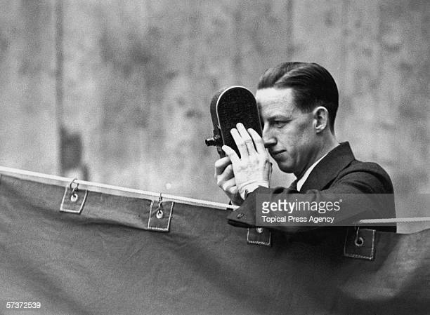 Jack Purcell, the Canadian champion, uses his cine-camera to record the play at the All England Badminton Championships in the Royal Horticultural...