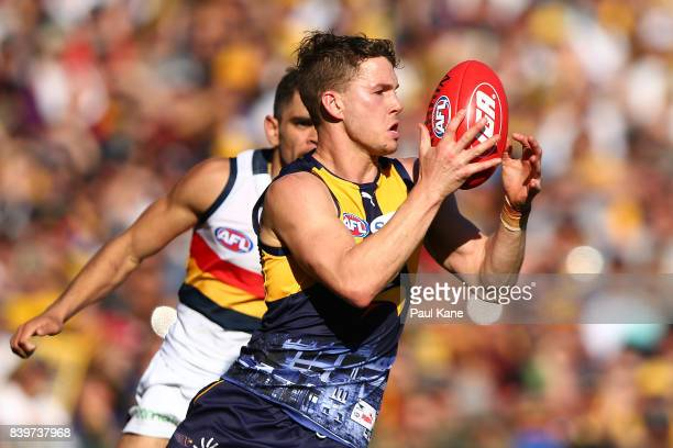 Jack Redden of the Eagles gathers the ball against Charlie Cameron of the Crows during the round 23 AFL match between the West Coast Eagles and the...