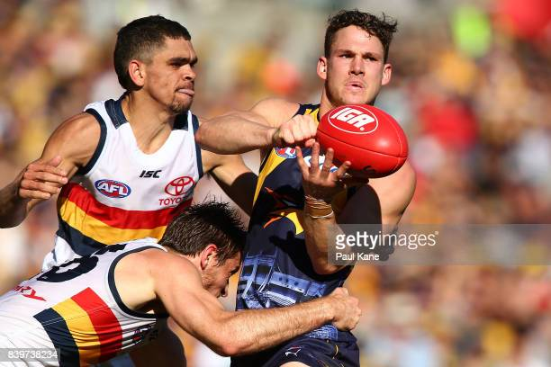 Jack Redden of the Eagles gets his handball away while being tackled by Richard Douglas of the Crows during the round 23 AFL match between the West...