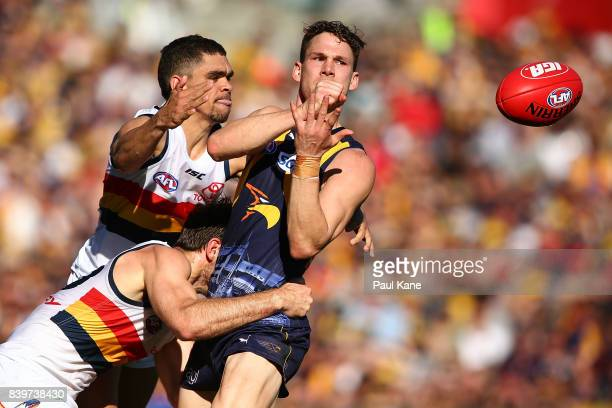 Jack Redden of the Eagles gets his handball away while being tackled by Charlie Cameron and Richard Douglas of the Crows during the round 23 AFL...