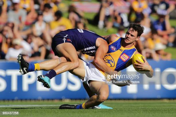 Jack Redden of the Eagles is tackled by Darcy Tucker of the Dockers during the JLT Community Series AFL match between the Fremantle Dockers and the...