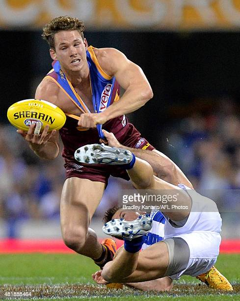 Jack Redden of the Lions attempts to break free from the defence of Brent Harvey of the Kangaroos during the round 17 AFL match between the Brisbane...