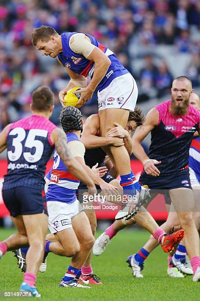 Jack Redpath of the Bulldogs gathers the ball and is hoisted up by Jack Viney of the Demons during the round eight AFL match between the Melbourne...