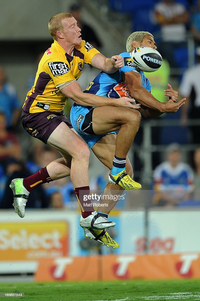Jack Reed of the Broncos (L) and David Mead of the Titans compete for the ball during the round five NRL match between the Gold Coast Titans and the Brisbane Broncos at Skilled Park on April 5, 2013 on the Gold Coast, Australia.