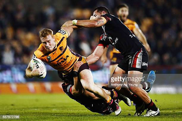 Jack Reed of the Broncos is tackled by Bodene Thompson and Nathaniel Roache of the Warriors during the round 13 NRL match between the New Zealand...