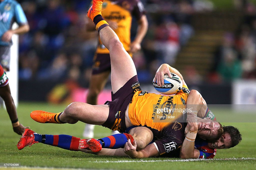 Jack Reed of the Broncos is tackled by Kurt Gidley of the Knights during the round 11 NRL match between the Newcastle Knights and the Brisbane Broncos at Hunter Stadium on May 25, 2015 in Newcastle, Australia.