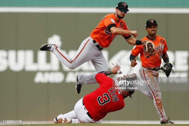Jack Reinheimer of the Baltimore Orioles turns a double play against Sandy Leon of the Boston Red Sox during the Grapefruit League spring training...