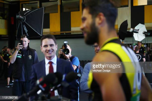 Jack Riewoldt of the Tigers films Trent Cotchin of the Tigers as he speaks to media during the AFL Richmond Tigers team photo session at Punt Road...