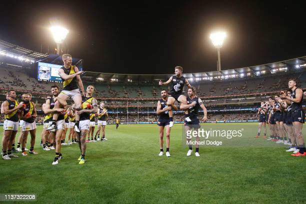 Jack Riewoldt of the Tigers gets carried off for his 200th game by Trent Cotchin and Dustin Martin and Marc Murphy of the Blues gets carried off by...