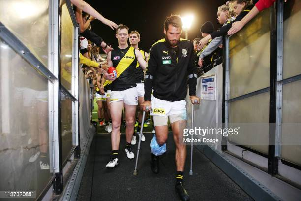Jack Riewoldt of the Tigers walks off with Alex Rance of the Tigers who sustained a leg injury during the round one AFL match between the Carlton...