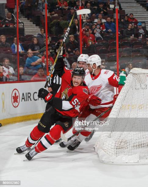 Jack Rodewald of the Ottawa Senators skates behind the net against Mike Green and Xavier Ouellet of the Detroit Red Wings at Canadian Tire Centre on...