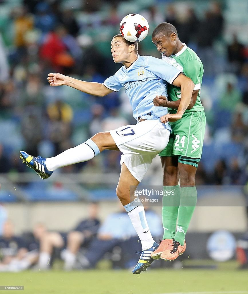 Jack Rodwell heads past Ramson Zhuwawo of AmaZulu during the Nelson Mandela Football Invitational match between AmaZulu and Manchester City at Moses Mabhida Stadium on July 18, 2013 in Durban, South Africa.