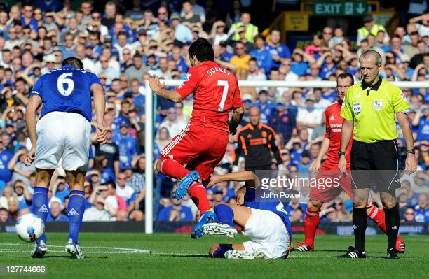 Jack Rodwell of Everton tackles Luis Suarez of Liverpool and is given a red card for the challenge by referee Martin Atkinson during the Barclays...