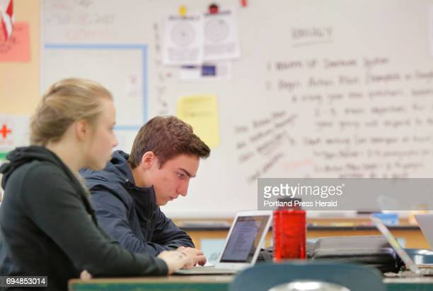 Jack Romano looks over his action plan for a mock press conference he is organizing with a group of other students in a science class at Yarmouth...