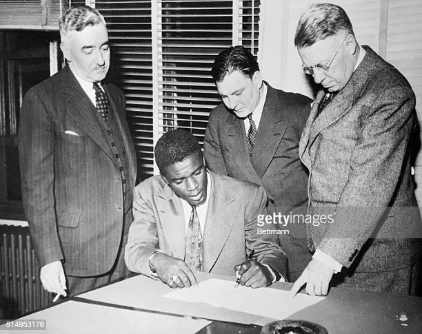 Jack Roosevelt Robinson the first Negro to win a contract in organized baseball is shown signing for the Montreal Royals of the International League...